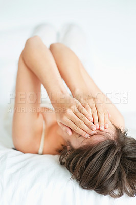 Buy stock photo Young woman covering her eyes while lying on bed