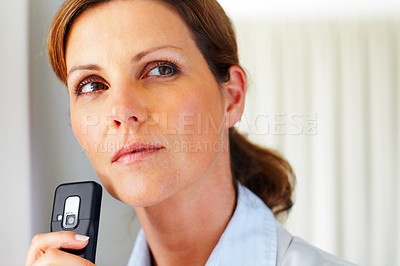 Buy stock photo Pretty young woman thinking with mobile phone