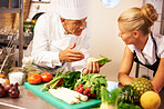 Chef explaining trainee about chopping vegetable