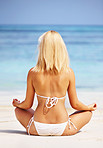 Woman in meditating at beach