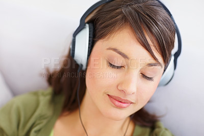 Buy stock photo Closeup of a pretty woman listening to pleasant music on her headphones