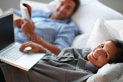 Buy stock photo Young couple reading and working on laptop.