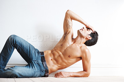 Buy stock photo Portrait of a relaxed young male fashion model posing while lying on floor