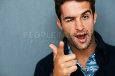 Buy stock photo Studio portrait of a handsome young man winking and pointing