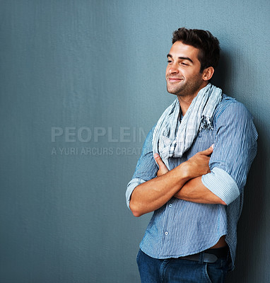 Buy stock photo Trendy young man in relaxed fashion leaning against a wall with arms folded, smiling - copyspace