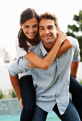 Buy stock photo Handsome man giving pretty woman piggy-back ride