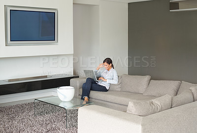 Buy stock photo Stylish woman sitting in a modern living room with her laptop - copyspace