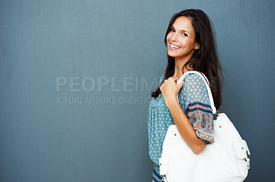 Buy stock photo Approachable woman holding purse against blue background