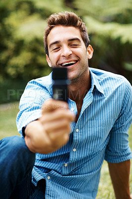 Buy stock photo Shot of a young man taking a photo with a cellphone in the park
