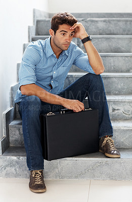 Buy stock photo Shot of a worried young businessman sitting on staircase