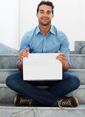 Buy stock photo Portrait of a smiling young man holding a laptop while sitting on staircase