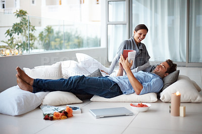 Buy stock photo Portrait of a young man reading book while relaxing with his girlfriend at home