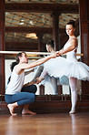 Young ballet trainer training a female ballet dancer