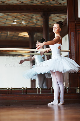 Buy stock photo Full length of a young and beautiful ballet dancer practicing against mirror
