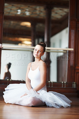 Buy stock photo Portrait of a young beautiful ballet dancer resting on wooden floor
