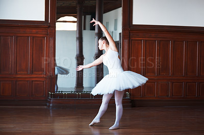 Buy stock photo Full length of a young ballerina wearing white tutu practicing in front of a mirror