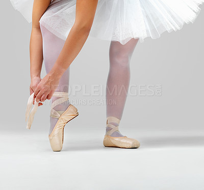 Buy stock photo Low angle view of a ballerina putting on her ballet shoes against white background