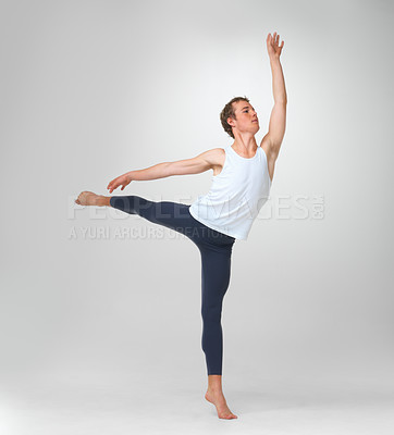 Buy stock photo Full length of a young ballet dancer performing a balancing act against white background