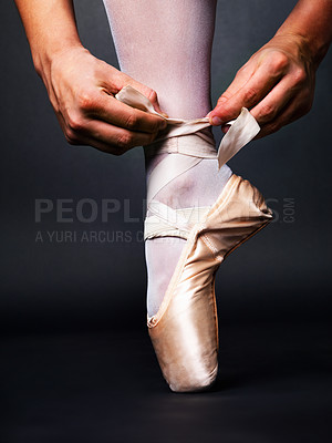 Buy stock photo Low angle view of a ballerina putting on Pointe against black background