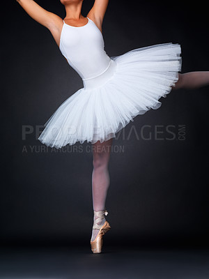 Buy stock photo Cropped image of a ballerina performing a balancing act in pointe shoes against a black background