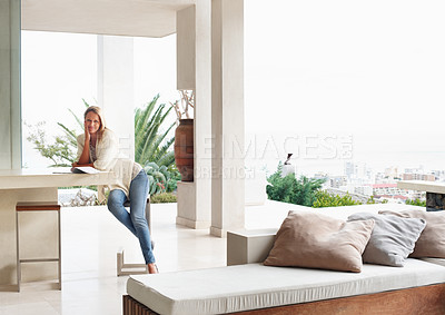 Buy stock photo Smiling woman sitting at a big living room with view of city