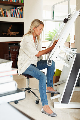 Buy stock photo Side view of a female architect working on a drawing board in her bright modern home