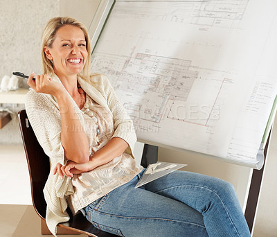Buy stock photo A cheerful female architect with her blueprint behind her
