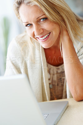 Buy stock photo Closeup portrait of a smiling middle aged woman working on a laptop