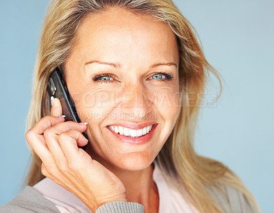Buy stock photo Closeup portrait of a mature woman using a cellphone against blue background