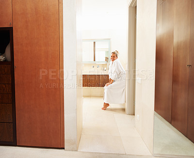 Buy stock photo Portrait of a happy mature woman in bathrobe sitting in modern house