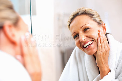 Buy stock photo A happy beautiful mature woman admiring herself in the mirror