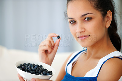 Buy stock photo Portrait of sweet young woman eating blueberries at home - Indoors