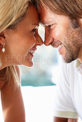 Buy stock photo Closeup portrait of a romantic mature couple head to head smiling lovingly at each other - copyspace