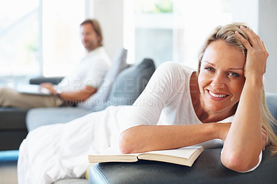 Buy stock photo Portrait of a relaxed mature woman lying on couch with man using laptop in the background at home