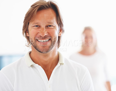 Buy stock photo Closeup portrait of a smart mature man smiling with woman in the background