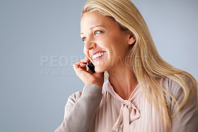 Buy stock photo Closeup of a smiling mature woman looking at copyspace while using a cellphone against blue background