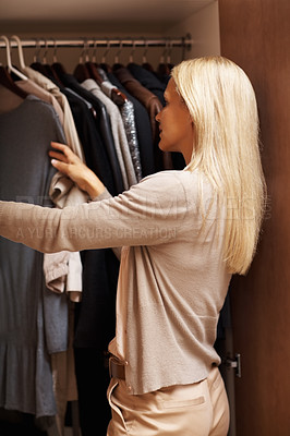 Buy stock photo Pretty female looking through her wardrobe and choosing clothes