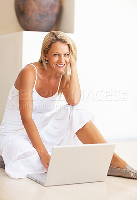 Buy stock photo Portrait of a smiling mature woman sitting on floor using laptop