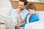 Little boy using laptop with his father reading newspaper on couch