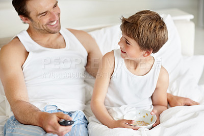Buy stock photo Portrait of little boy eating his breakfast with his father holding a tv remote control on bed