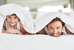 Happy young father and son together under bedsheet