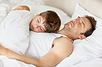 Young father and son sleeping together on bed