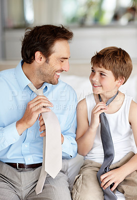 Buy stock photo Portrait of a happy young father and his son holding necktie and looking at each other
