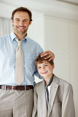 Buy stock photo Portrait of a caring young father standing with his son wearing an oversized coat