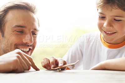 Buy stock photo Portrait of a happy young man and his son playing with a tiny skateboard