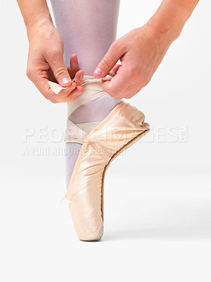 Buy stock photo Low angle view of a ballerina putting on Pointe against white background