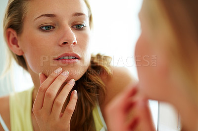 Buy stock photo Closeup portrait of a cute young woman looking her face in the mirror