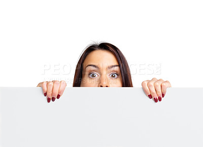 Buy stock photo Portrait of a young woman peeping over a empty billboard against white background