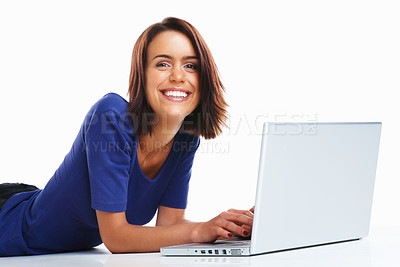 Buy stock photo Happy female student casually lying on floor with a laptop against white