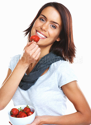Buy stock photo Portrait of a young woman eating a bowl of fresh strawberries against white background